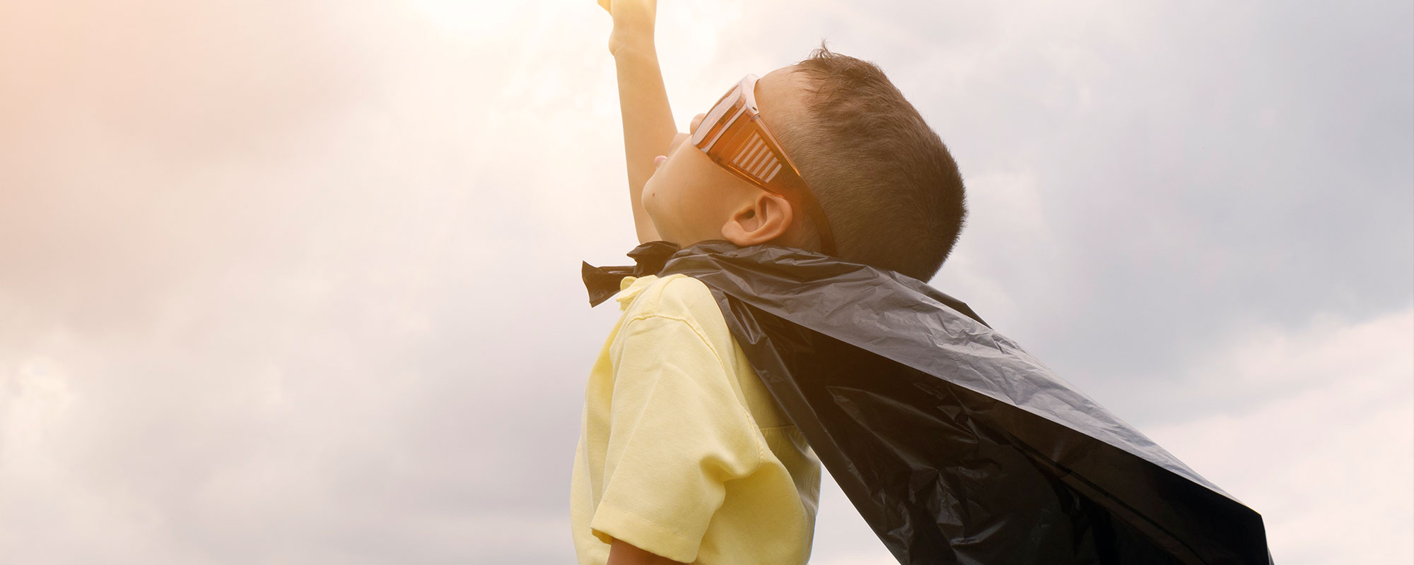 child with a cape pointing to the sky