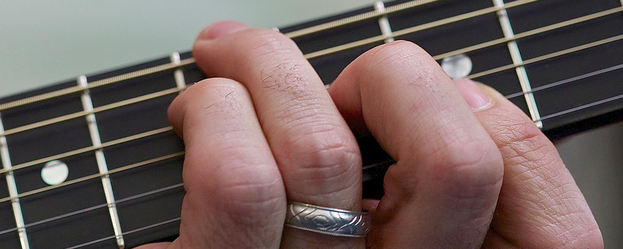 fingers playing a chord on a guitar