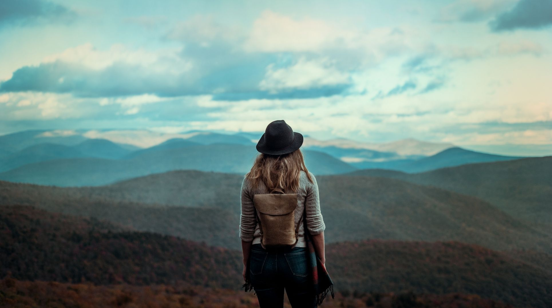 woman with backpack looking out over mountain landscape